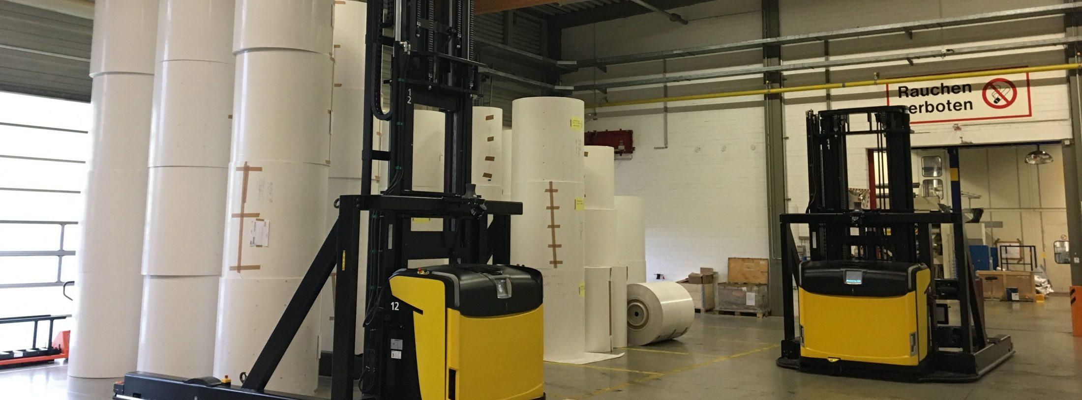 Produktionslogistik im Papierlager. Bild zeigt den Transport von Papierrollen mithilfe eines speziellen Gabelstaplers.