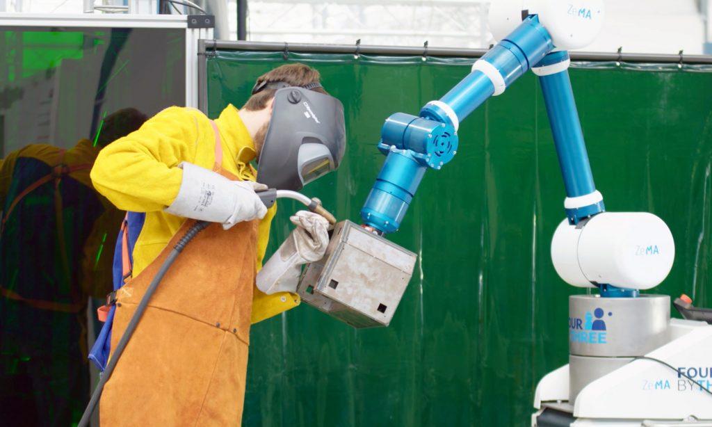 FourByThree-Prototyp in der Anwendungsstudie bei der Firma WOLL (Deutschland): Der Roboterarm unterstützt einen Menschen bei Schweißarbeiten durch Halten und Positionieren des Werkstücks während des Schweißprozesses. (Bild: Intelligenz (DFKI) Deutsches Forschungszentrum für Künstl.)