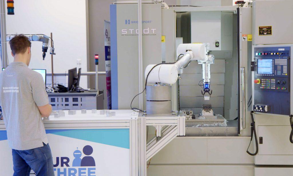 Anwendungsstudie bei der Firma STODT (Niederlande): Einer der im Projekt FourByThree entwickelten Roboterarme unterstützt einen Arbeiter bei der Be- und Entladung einer Maschine mit Bauteilen. Die FourByThree-Steuerungssoftware soll dabei die Automatisierung von wiederholenden Tätigkeiten für Kleinserien erleichtern. (Bild: Intelligenz (DFKI) Deutsches Forschungszentrum für Künstl.)