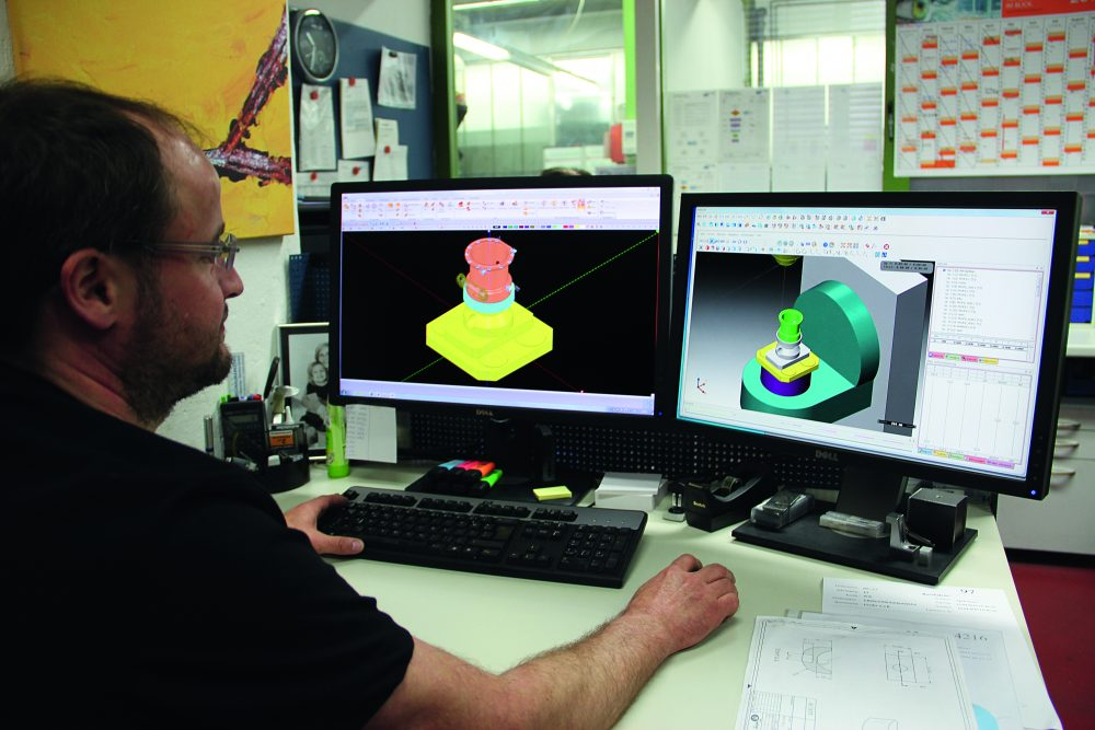 Schritt für Schritt zum Virtual Machining - Ein Mitarbeiter lässt eine Simluation einer NC-Programmierung über seine Rechner laufen