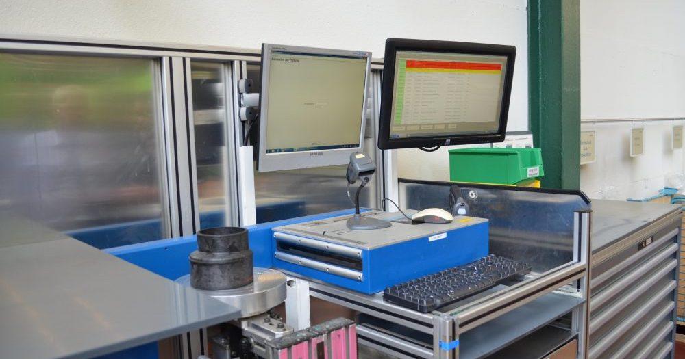 An einem Prüfplatz misst ein Laserscanner die Abmessungen einer exzentrischen Schallschutzreduktion automatisch, die Prüfaufträge werden über das GRP-MES angezeigt.