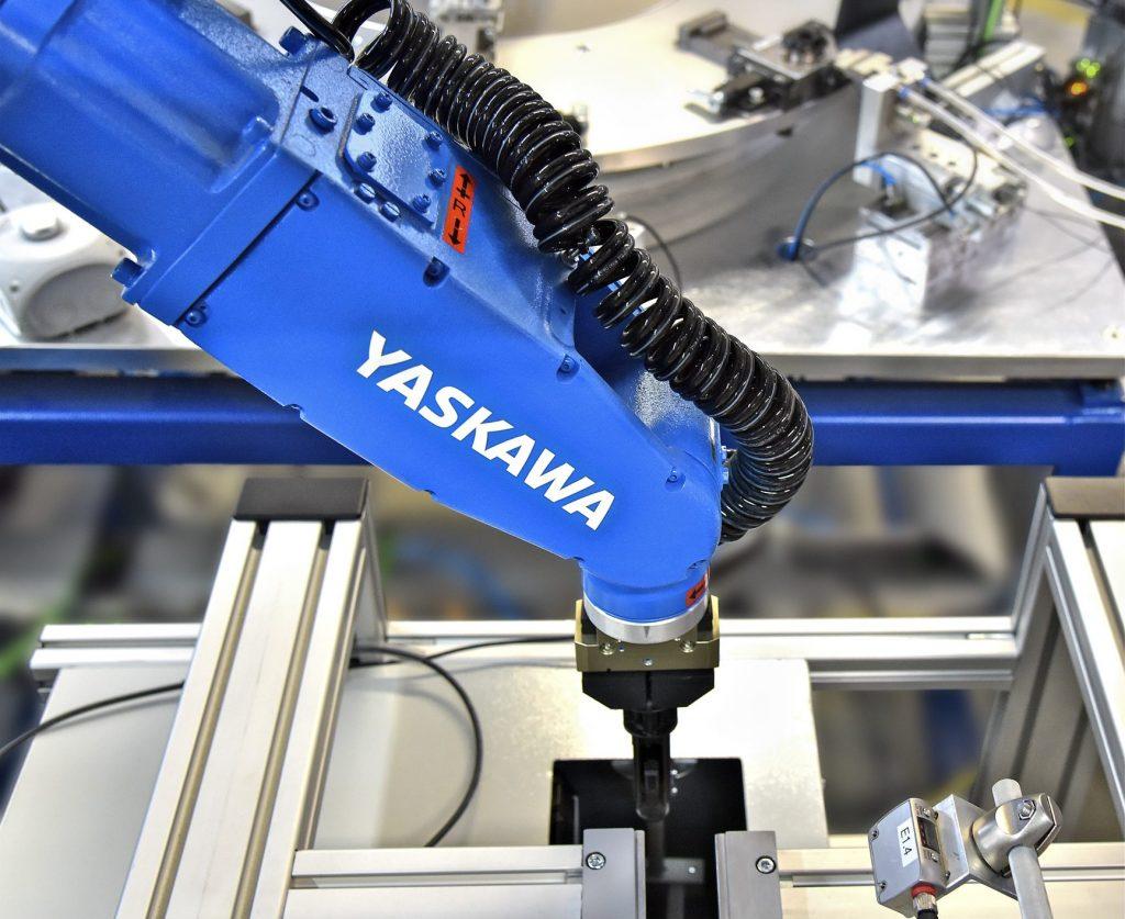 Montage von Führungshülsen für Kopfstützen: Der Roboter fährt mit dem Teil ein stationäres Visionsystem an, das die Teilenummer einliest. (Bild: Yaskawa Europe GmbH)
