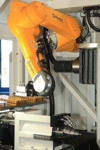 Roboter mit Feingefühl: Der Stäubli-Roboterarm automatisiert die Bestückung der Werkzeugaufnahme in der Strausak-Schleifmaschine. (Bild: Dr. Johannes Heidenhain GmbH)