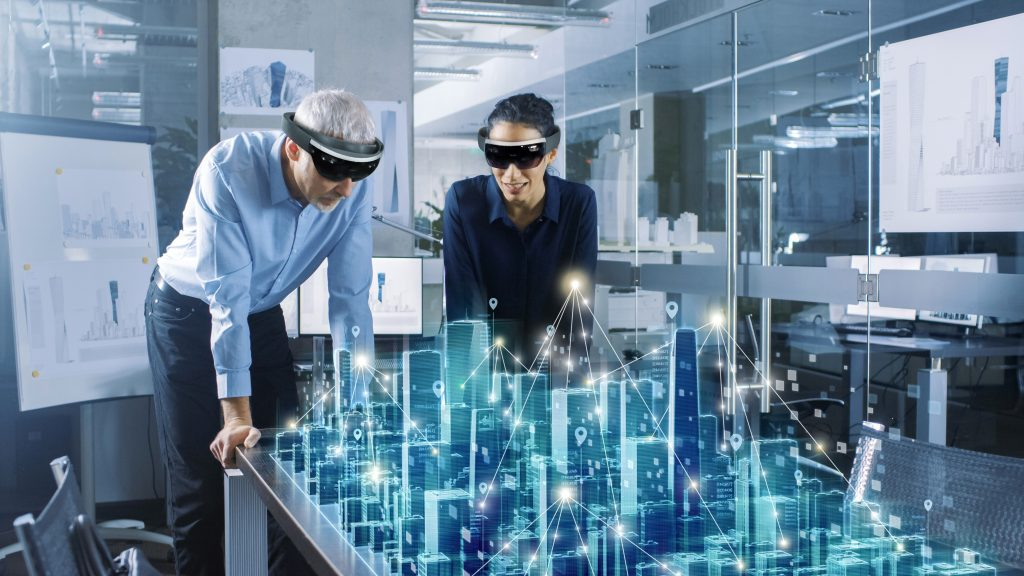 Male and Female Architects Work with Holographic Augmented Reality 3D City Model. Technologically Advanced Office Professional People Use Virtual Reality Modeling Software Application. (Bild: Atos Information Technology GmbH)