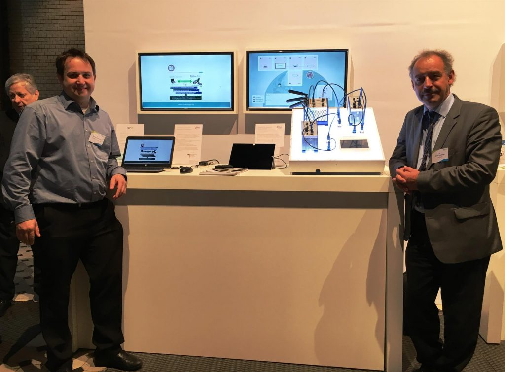 Dr. Detlef Houdeau (rechts) und Dr. Florian Schreiner vor dem Demonstrator von Infineon: dieser zeigt, wie sich Router mit Hilfe von TPMs gegenüber dem Produktionsnetzwerk authentifizieren können. (Bild: Infineon Technologies AG)