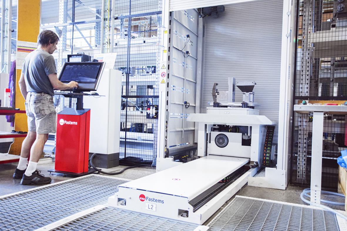 Am Bedienpult der Automatisierungsanlage spannt der Mitarbeiter das Werkstück auf die Vorrichtung, die dann automatisch in die Maschine fährt. (Bild: ©Daniela Glunz/Cosmo Consult SSC GmbH)