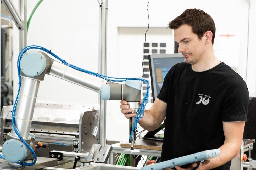 Im Freilaufmodus greift Sebastian Schuler den Arm des Roboters und bringt ihm Aufgaben bei, indem er ihn physisch von Wegpunkt zu Wegpunkt führt. (Bild: Universal Robots (Germany) GmbH)